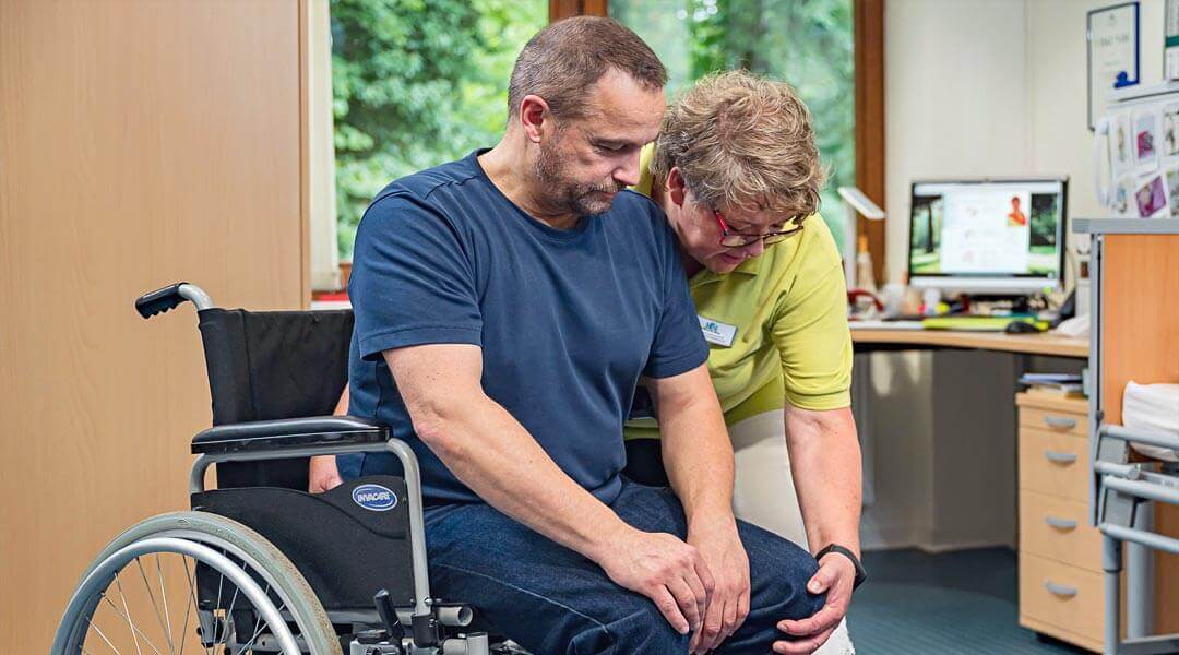 Maria Kukuk übt die Bewegungsfähigkeit mit Patient im Rollstuhl