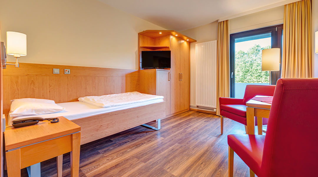 Patientenzimmer mit Bett und TV in der Caspar Heinrich Klinik