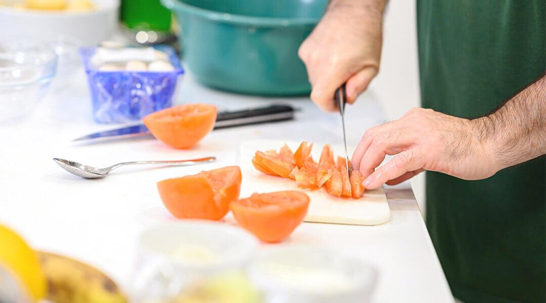 Person schneidet eine Tomate in der Lehrküche Caspar Heinrich Klinik