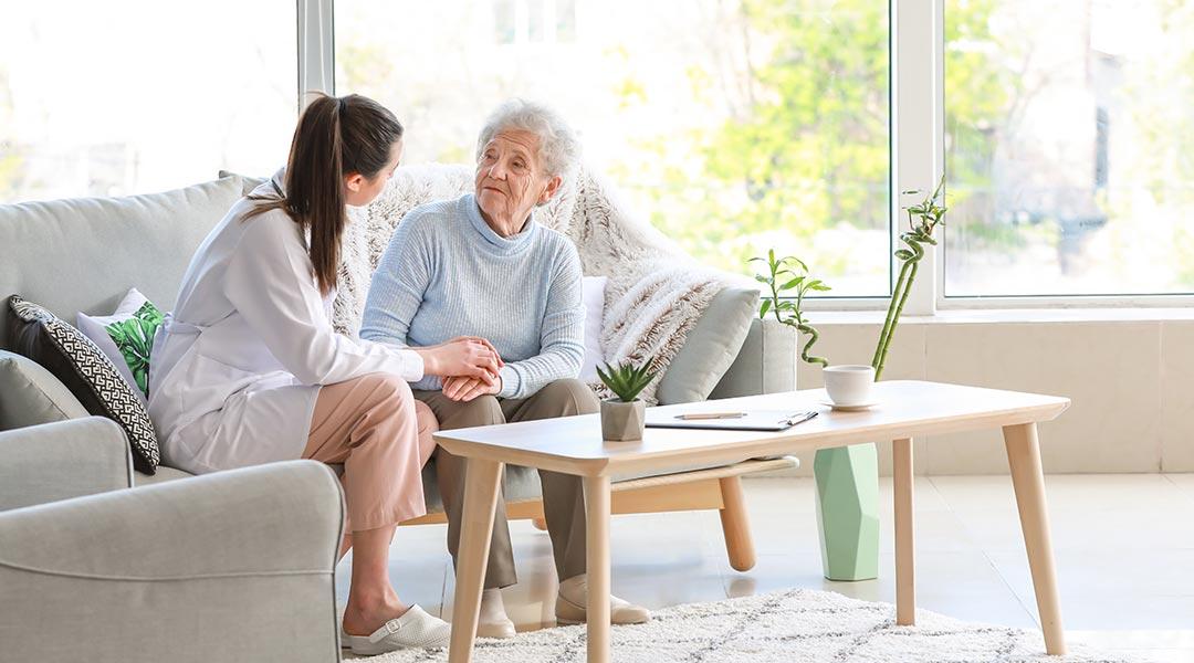 Pflegerin besucht älter Dame beim Hausbesuch