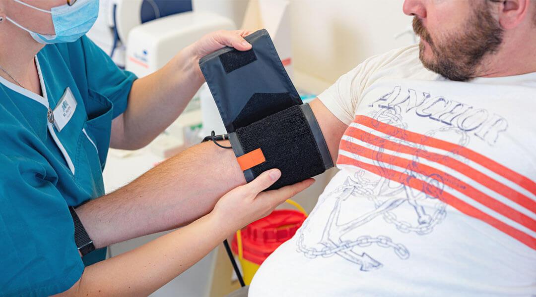 Pflegerin misst Blutdruck bei einem Patienten