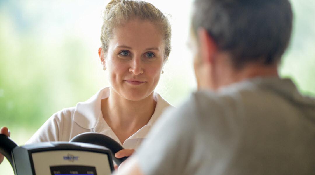 Therapeutin erklärt Ergometer in der Sporttherapie der Caspar Heinrich Klinik